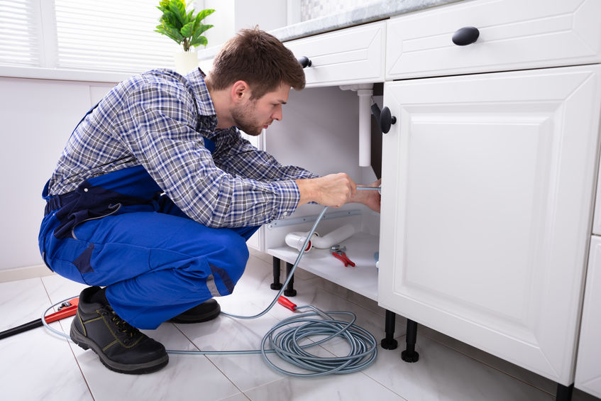 young male plumber cleaning a clogged kitchen sink