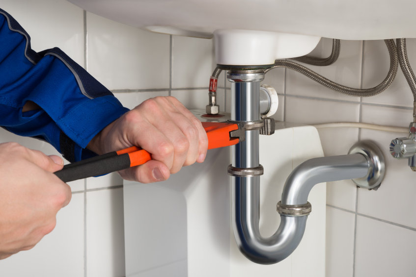 close-up of male plumber's hands with wrench fixing a drain pipe