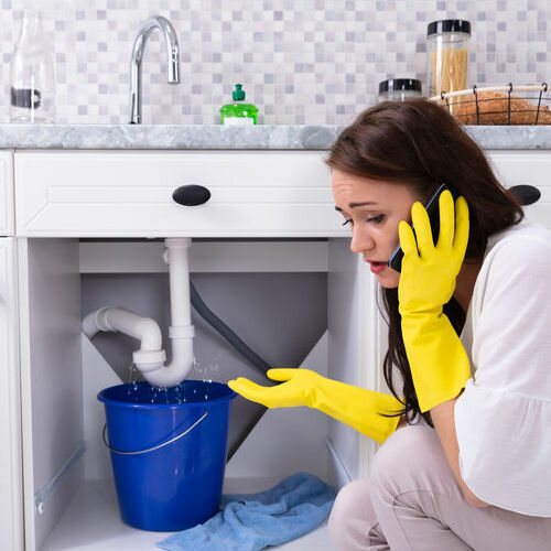A young woman calling a plumber in front of water leaking from sink pipe.