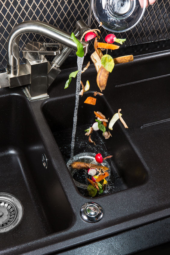food being dropped into garbage disposal in sink