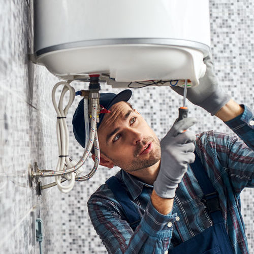 Worker setting up an electric heating boiler at home.