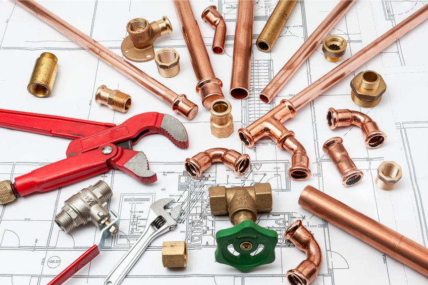 plumbing tools arranged over house plans