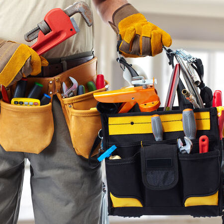 close up of a builder handyman with construction tools.