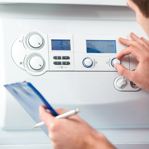 technician servicing or inspecting a gas boiler for hot water and heating