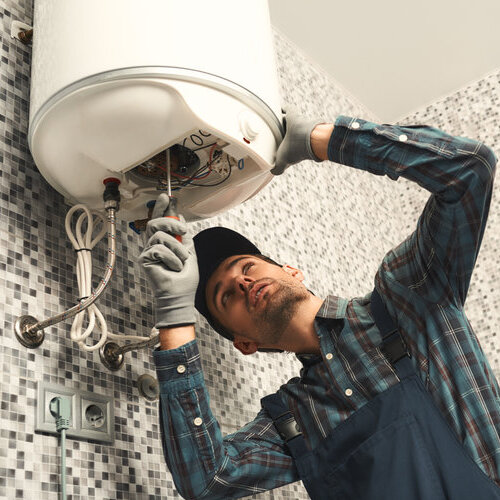 A young handyman in uniform setting up electric heating boiler at home.