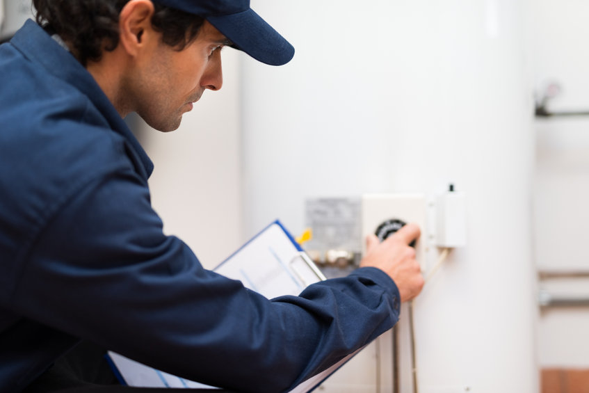 Technician adjusting a regulator of a water heater/boiler.